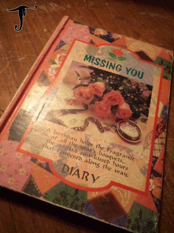 buku diary berwarna pink dengan sampul bunga mawar dan arloji